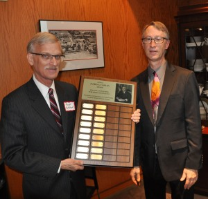 Roger Ruthhart (left) of the Moline Dispatch accepts the 2016 news competition sweepstakes trophy Thursday from the group's executive secretary Jason Akst. The award was presented at NINA'a annual banquet held at Northern Illinois University.